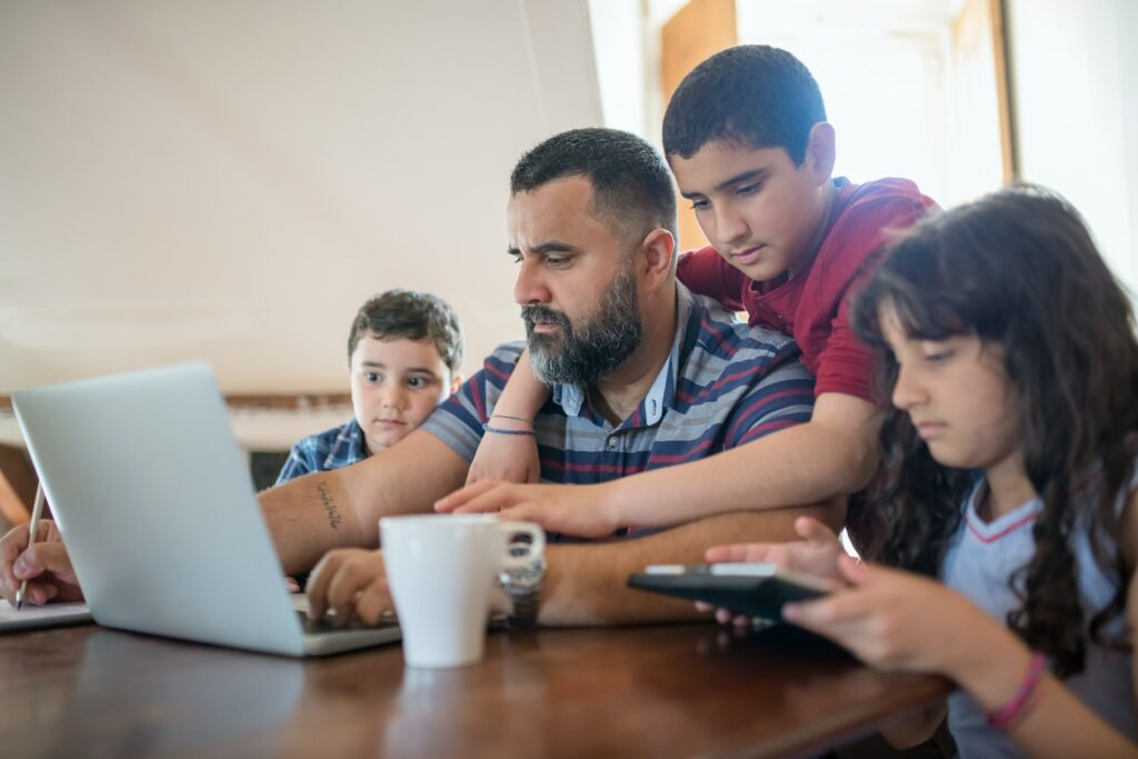 A father with children at a table with laptop, note pad and calculator - symbolizing the joint budgeting process of the family