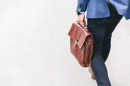 An Investment expert in a blue suite, carrying a briefcase