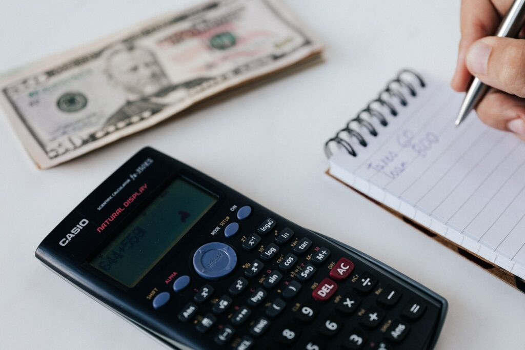 A calculator, some money and someone writing expenses on a notepad - symbolizing the budgeting process