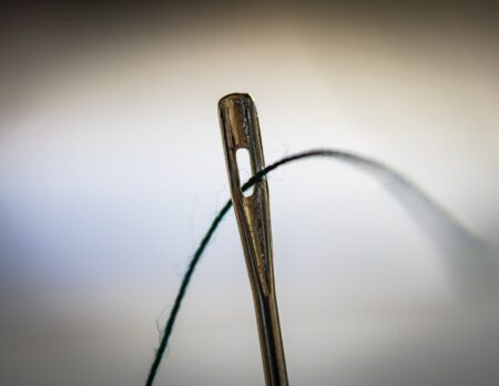 Threading a needle, symbolizing the complexity of a budget for the 4-year college project
